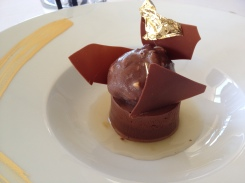 This was a base of chocolate mousse with ice cream covered in chocolate. Notice the the edible gold leaf.